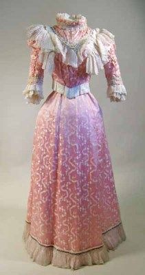 1899 two-piece evening or dinner dress in pink silk, figured with delicate meandering cream floral motifs, and trimmed with cream moire ribbon and fine cream silk and sead pearls. Waistband printed in black: 'The Misses Brierley, Costumiers, Cheadle Hulme'.  Via Manchester City Galleries.