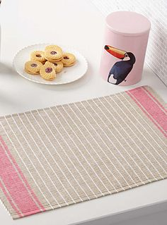 Designed in our studios exclusively for Simons Maison Add a touch of candy pink to your meals with a woven place mat accented by stripes at the ends. - Textured 100% cotton weave - Machine wash and dry - 33 x 50 cm