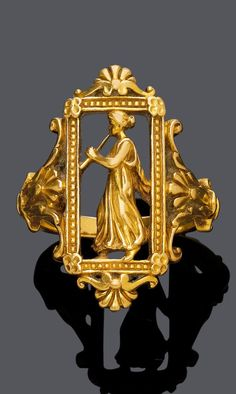 WIÈSE - AN ANTIQUE GOLD RING, FRENCH, CIRCA 1900. Of openwork design, depicting a female flute player, the frame and ring shoulders enhanced by palmette motifs. Engraved Wiese, French gold marks.