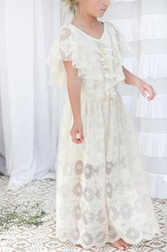 Stunning lace maxi dress in gorgeous ivory and dark cream tones. This dress features a flutter style lace sleeve and lace ruffle detail at the front. Satin ribb