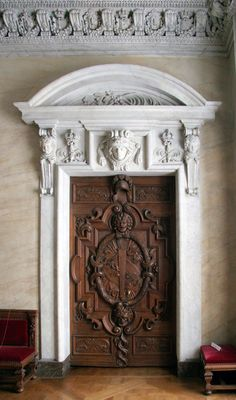 A massive carved panel door with marble surround at Fontainebleau