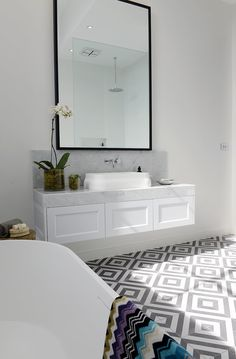 Floating vanity, thick marble slab counter, tile floor and large mirror