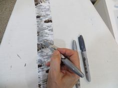 Start with the metallic silver Sharpie and shade the left 1/3 - 1/2 side of the tree. Use a horizontal motion and color all the way down the trunk.