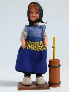 Eine rothaarige Frau in Tracht von Raalte, Niederlanden. Schwarzer Rock, weißkarrierte Bluse und Schürze mit unterschiedlichen Mustern in den Farben Blau und Gelb. Holzschuhe und schwarzes, unter dem Kinn gebundenes Kopftuch. Zur Puppe gehört ein Butterfaß aus Holz. #Overijssel #Salland