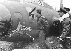 "Luftwaffe fighter ace Heinrich Bär wearing a captured USAAF bomber jacket while inspecting his 184th victory, the B-17F ""Miss Ouachita""."