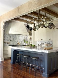 Filled with rustic charm, this gorgeous ivory and blue kitchen boasts a pot rack mounted to a ceiling accented with rustic wood beams above a blue center island seating three Crate & Barrel Turner Gunmetal Adjustable Backless Bar Stools in front of a thick marble countertop fitted with a sink and a antique deck mount faucet.