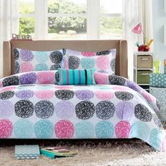 Showcase color in her bedroom with this comforter set featuring abstract circles in bright shades of pink, teal, purple and black.