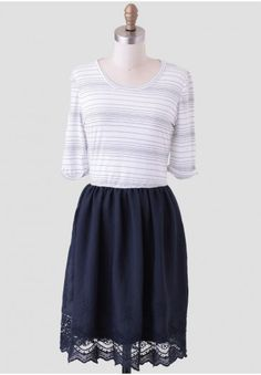 <p>This darling dress features a white top with thin black stripes, three-quarter length sleeves and a solid navy skirt. Perfected with a scalloped lace eyelet trim around the hem of the skirt, this charming dress is a back-to-school must-have that pairs perfectly with flats and a structured satchel. Fully lined.<br /> <br /> Self: 93% Rayon, 7% Polyester<br /> Lining: 100% Polyester<br /> Made In USA<br /> 30