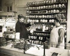 Een ambtenaar van de Keuringsdienst van Waren keurt een brood door het te wegen met een handweegschaaltje. Hij staat achter de toonbank in de winkel van de bakker, naast de verkoopster. In de schappen achter hen liggen rijen broden . Op de toonbank liggen verschillende koeken. [Amsterdam], 1926.