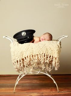 Amanda Abraham Photography specializing in newborn and child family photography. Newborn neutral color scheme with using colors close to the skin tone to make the newborn stand out. Photographer in the Metro Detroit, Michigan area with a home studio, using props and textured blankets with posing to add to a whimsical newborn portrait photo experience! Posing with father's police officer cap.