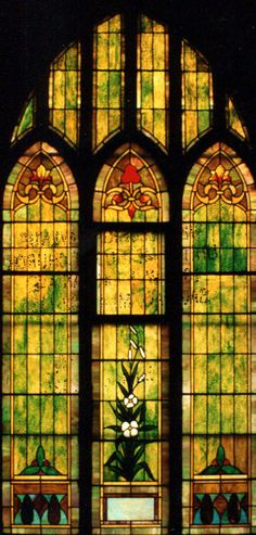 A series of ornamental windows with the center window containing a white flower. West Michigan Avenue United Methodist Church, Saginaw, MI
