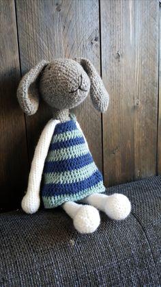 Dit konijn is gemaakt van grijs en wit garen en heeft een jurk aan.