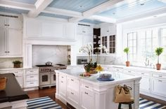 I love the stripey floor rugs and the pale blue ceiling in this Greenwich kitchen