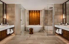 One&Only Ocean Club - The gorgeous, egg-shaped bathtub is offset by a walnut backsplash, which balances the hard surfaces in the space with its warmth and texture.