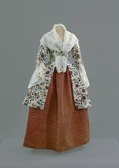 Jacket of India Chintz cotton, shown with an embroidered cotton kerchief and ruffles and a wool quilted petticoat. The petticoat was made in New England between 1755-75. Colonial Williamsburg