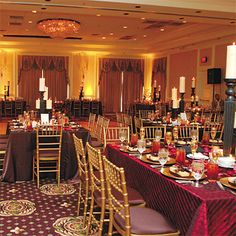 Brides: Red and Gold Wedding Reception Decor. Gold chiavari chairs and dinnerware from We Rent Atlanta, and linens from wildflowerlinens.com, filled the ballroom with jewel-tone embellishments. Instead of floral centerpieces, candles from gardenridge.com and pillars from Z Studio Gallery graced the tables.