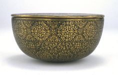 Bowl (with lid). Hemispherical bowl with flat lid. Decoration consists of roundels and friezes of foliate ornament. Made of raised brass, engraved and inlaid (metal inlay now missing, black substance remains).  Mamluk dynasty; Islamic; 15thC(late); Syria; Egypt; Palestine