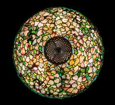 A Tiffany Studios Favrile Glass and Bronze Dogwood Lamp, the shade of flattened dome form, with allover dogwood decoration in shades of white and pink against a confetti ground, the shade ending in two geometric bands, raised on a Tyler base, the font and the base stamped Tiffany Studios New York 179.