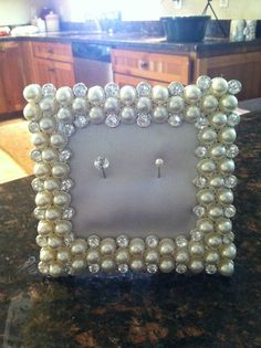 DIY ring holder wedding gift. Fabulous pearl and rhinestone picture frame that i bought at hobby lobby (it's basically a Joanne's or micheals) and bought a plain cork drink coaster and covered it in a cream/ivory poly-satin and stuck two cute pins on the cork so they can put their rings on there to hold them. Love!!!
