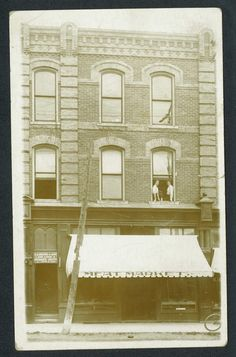 This photo shows two women looking out of their apartment window at 195 Broadway in the 1920's, above D.B. Brown & Son's Land loan and Insurance Office, and the local meat market.