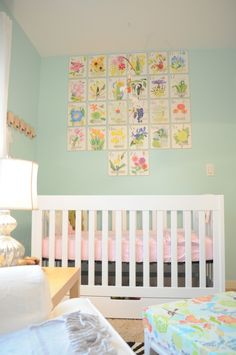 #Floral prints add a feminine touch to a #blue girls' #nursery.
