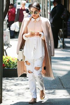 Vanessa Hudgens wears a color blocked button-down shirt, pink coat, ripped white jeans, flats, a white bag, and round sunglasses