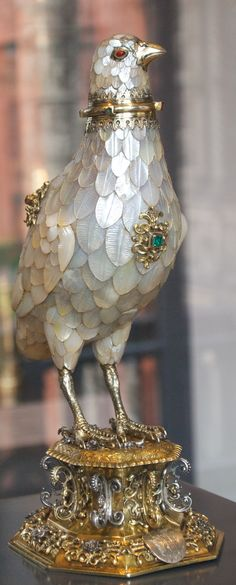 Silver-gilt, gold, gems and mother of pearl cup in the form of a partridge with feathers of overlapping mother of pearl; removable head with gem set eyes, standing on an octagonal plinth. 1598-1602. Height: 27 cm, Width: 14 cm, Depth: 10.5 cm, Weight: 1000 g. This cup is notable for the naturalistic effect of the carving. A similar cup by the 16th-century Nürnberg goldsmith Friedrich Hillebrandt can be found in Dresden.