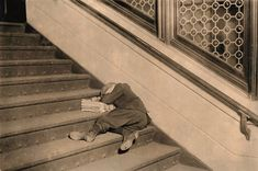 An exhausted newsboy sleeps on a pile of newspapers in a stairwell in Jersey City, New Jersey, circa 1912.