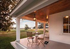 Porch. Porch Steps. Front Porch. Wrap around Porch. Farm, farmhouse, folding chair, folding table, gray floor porch, lantern pendants, lemonade, painted floor, porch lighting, porch seating, white siding, wood ceiling, woven patio chair woven table top, wraparound porch. #porch