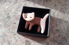 Woodwork and bonework. A handmade cat shaped brooch made from oak and bone. I made this piece of jewelry for my mother.