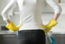 Rear, closeup view at young woman hands at her hips by fizkes. Rear, closeup view at a young woman wearing rubber protective yellow gloves, holding rag and spray bottle detergent, . Yellow Gloves, Clean Bathtub, Business Photos, Photoshop Photography, Modern Graphic Design, Clean House, Young Women, Close Up, Women Wear