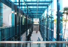 the gallery walkway extends from an existing two storey retail building, and is composed of blue-colored glass fins connected and reinforced by minimally expressed steel elements.