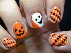 Happy Halloween pumpkins nail art. Decorate your nails in orange, black and white polish forming smiling pumpkin and ghost faces. You can also add polka dot designs.