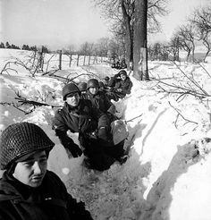 American soldiers in a snowy ditch somwhere in Belgium during the counter offensive which would become known as the Battle of the Bulge