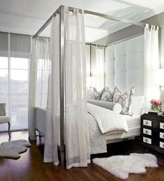 Gorgeous gray bedroom with gray wallpaper, metal canopy bed, white tufted headboard, linen panels, Ikea Rens Pelts, espresso wood nightstands, white  gray trellis shams, gray bolster pillow  duvet. by valerie