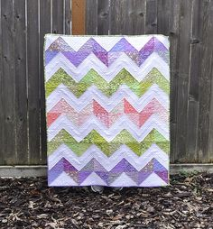 Zigzag quilt down with charm squares made into half square triangles. Straight line quilting on the white and stipple on the colors
