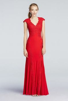 Red hot and regal with classically sexy details, this lace dress will have everyone's eyes on you at this year's Prom!  This beautiful floor length dress features a cap sleeve bodice, complete with gorgeous lace applique detail that extends into godets for an ultra-flattering, streamlined silhouette.  Eye-catching v-neckline and illusion back add plenty of allure for an elevated Prom look.  Designed by Betsy
