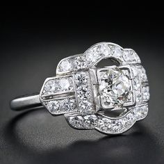 This is a sleek and low profile ring from the Art Deco period from Whitehouse Bros. A .40 carat European cut diamond is set in a square box setting and fully surrounded by accent diamonds finished with fine milgrain detailing. An easy to wear, stand alone ring. Stamped 'W' for Whitehouse Bros and inscribed with the initials 'A.P.H.'.