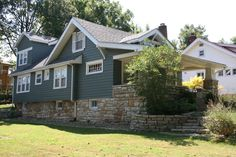 Wood siding and brick exterior. Blue/gray paint with white trim.