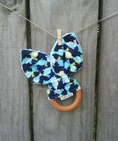 GORGEOUS BUNNY TEETHING RING  ----------- $14 ------------   This beautiful teething ring is made from maple hardwood, hand brushed with organic olive oil and beeswax.  Bunny Ears are 100% cotton print & dimple dot minky fabric.  The beautiful matching dribble bib is also for sale in our Shop (shown in a separate photo).    Kindly donated by Little Mint Boutique: www.facebook.com/littlemintboutique