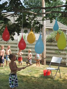 A Backyard Water Party featuring water balloon piñatas, colored kool-aid ice cubes, fence mural finger painting, & shaving cream pool.