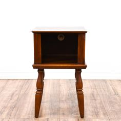 This end table is featured in a solid wood with a glossy cherry finish. This country style side table has carved turning legs and a spacious cabinet w/ a round opening in the back. Perfect place for a telephone! #countryfarmhouse #tables #endtable #sandiegovintage #vintagefurniture