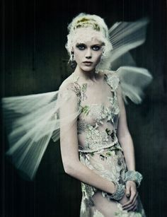 ethereal 1920's woman with pleated 'wings' and sheer flower embellished gown