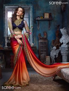 Drape yourself in luxury – with this smooth, skin skimming and form flattering vibrant saree in multiple shaded effect in cascading colors of dreamy peach, orange, red and purple…Accentuated with a very charming blue and gold border, this saree is paired with a super stylish and royal navy blue and gold choli that will be your perfect partner for many other sarees and ensembles too…
