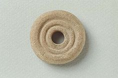 Viking era stone (sandstone?) spindle whorl with concentric decorations from Björkö (Historiska museet)