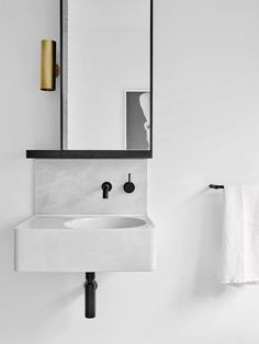 simple white modern floating vanity sink + black fixtures + brass sconce | interior style