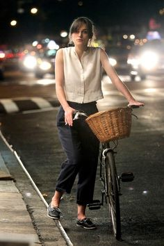 """Keira Knightley rides a bike on the set of her latest film, """"Can A Song Save Your Life?"""" in NYC. The actress wears a billowy white top and navy blue capri pants as she bikes around and then stows her bike in a bike rack."""