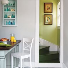 Blocks of unexpected green on the back staircase walls and steps enliven the area around the peninsula. Paint: Benjamin Moore's Pale Sea Mist (stairwell walls), Guacamole (stairs)