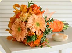 I love the look of gerbera daisies!!! Red though. maybe a silver ribbon. Bridesmaid bouquet