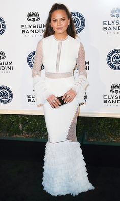 CHRISSY TEIGEN wore a Johnathan Simkhai gown with tiered ruffles at the hem and sleeves and sheer inserts, plus L'Dezen earrings to the Art of Elysium Gala.